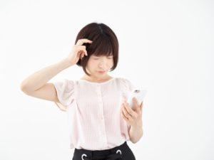 頭を抱えながらスマホを操作する女性