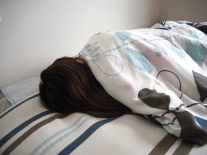 背を向けて眠る女性